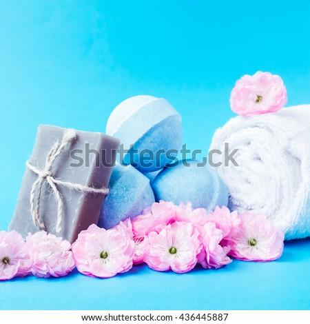 Beauty spa, bath bomb, aroma cosmetic soap with towel and soap bar with flower branch. Natural aromatherapy ball for care, wellness, health, treatment, hygiene, relaxation. - stock photo