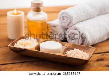 beauty, spa, body care, natural cosmetics and bath concept - close up of soap natural cosmeticshimalayan salt and scrub in wooden bowl on table - stock photo