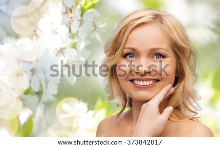 beauty, spring, skincare and natural cosmetics concept - smiling woman with bare shoulders touching face over cherry blossom background - stock photo