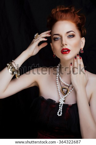 beauty stylish redhead woman with hairstyle and manicure wearing jewelry holding glass of vine - stock photo
