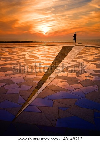 Beauty sunset with a human silhouette and with a beautiful tiling in diagonal composition in the foreground. - stock photo