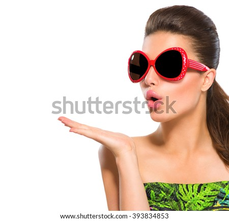 Beauty surprised fashion model girl wearing red sunglasses, with bright makeup showing empty copy space on open hand palm for text isolated on white background. Beautiful woman, summer fashion - stock photo
