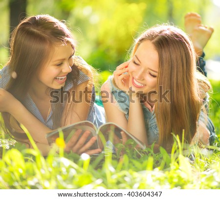 Beauty teen girls reading magazine and having fun outdoors. Beautiful joyful teenagers lying on spring grass, laughing and reading fashion magazine in spring park. Girlfriends outdoor. Friendship - stock photo