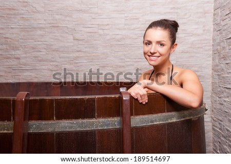 Beauty treatment. Beautiful young woman sitting in a barrel with water and smiling - stock photo