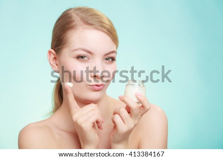 Beauty treatment. Woman applying moisturizing cream on face, holding jar with skin care product, studio shot on green blue background - stock photo