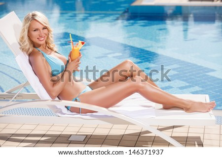 Beauty with cocktail. Attractive young women in bikini lying on the deck chair near the pool and holding a cocktail in her hand - stock photo