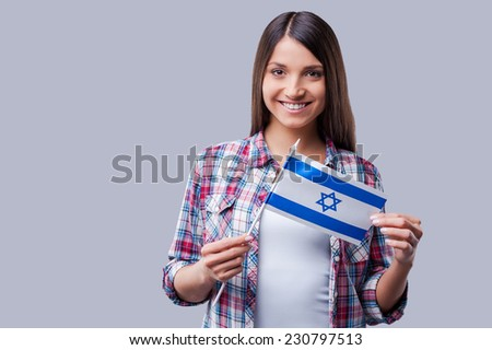 Beauty with Israeli flag. Happy young women holding flag of Israel while standing against grey background - stock photo