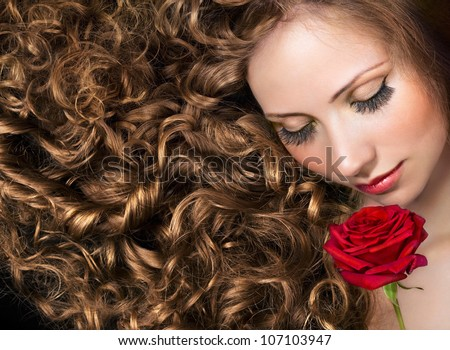 Beauty with long curly hair and red rose - stock photo