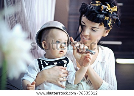 Beauty woman and baby with saucepan - stock photo