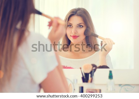Beauty woman applying makeup. Beautiful girl looking in the mirror and applying cosmetic with a big brush. Girl gets blush on the cheekbones. Powder, rouge - stock photo