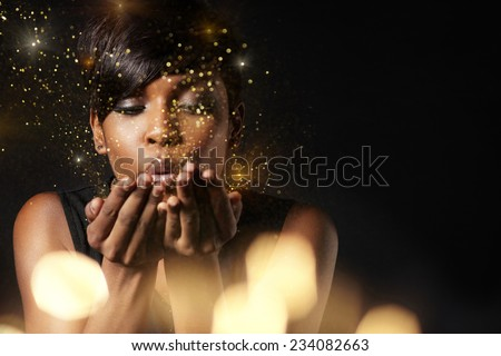 beauty woman blowing golden dust to the camera. Make a wish concept. Flair - stock photo