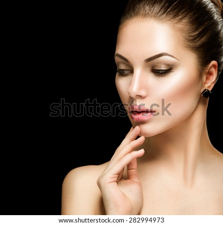 Beauty woman face closeup isolated on black background. Beautiful model girl makeup. Gorgeous sexy brunette lady touching her skin. Perfect make up - stock photo