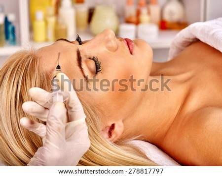 Beauty woman giving botox injections on forehead. - stock photo