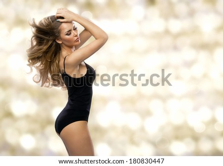 Beauty woman in black lingerie on gold background  - stock photo