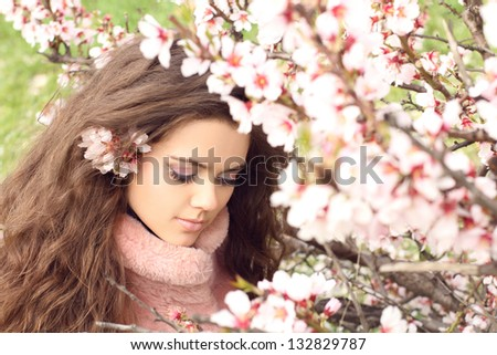 Beauty woman, outdoors portrait of teen girl beautiful cheerful enjoying with long brown hair over pink blossom background - stock photo