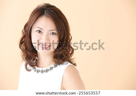 Beauty Woman Portrait. Healthy Long Curly Hair. Beautiful Young Woman isolated on a beige background - stock photo