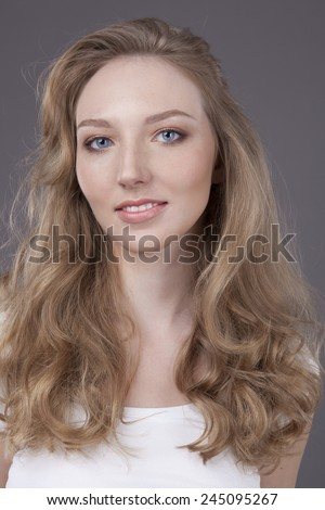 beauty woman portrait of teen girl beautiful cheerful enjoying with long blonde hair and clean skin isolated on grey background - stock photo