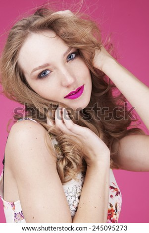 beauty woman portrait of teen girl beautiful cheerful enjoying with long blonde hair and clean skin isolated on pink background,bright make up,pink lips,colorful top - stock photo