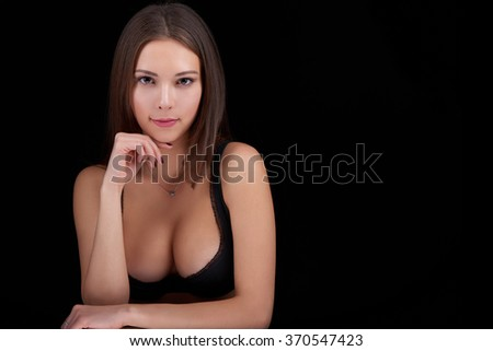 Beauty woman portrait posing in black bra showing her ample cleavage, over black background - stock photo