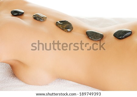 Beauty woman relaxing in spa. Hot stone massage.  - stock photo