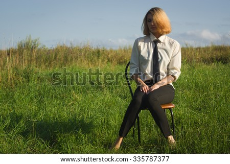 Beauty woman sitting in the armchair at the field and looking in expanse  - stock photo