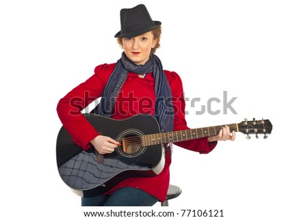Beauty woman with black hat and red jacket sitting on chair and playing acoustic guitar isolated on white background - stock photo