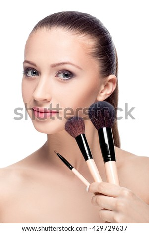 Beauty woman with Makeup Brushes. Natural Make-up for Brunette girl with Blue Eyes. Beautiful Face. Makeover. Perfect Skin. Applying Makeup - stock photo