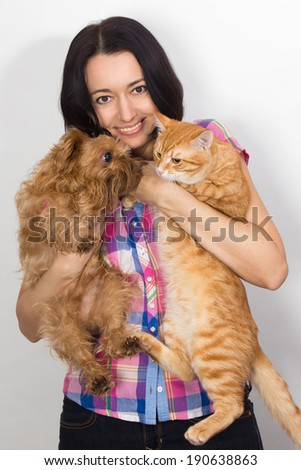 Beauty woman with orange domestic cat and griffon dog on his hands - stock photo