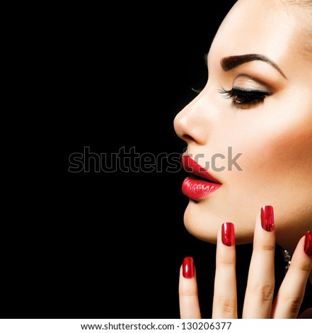 Beauty Woman with Perfect Makeup. Beautiful Professional Holiday Make-up. Red Lips and Nails. Beauty Girl's Face isolated on Black background. Glamorous Woman - stock photo