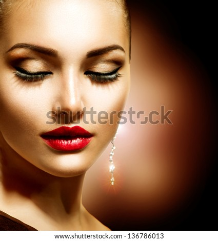 Beauty Woman with Perfect Makeup. Beautiful Professional Holiday Make-up. Red Lips Beauty Girl's Face isolated on Black background. Jewelry - stock photo