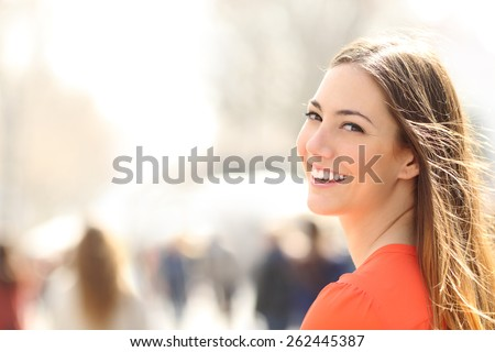 Beauty woman with perfect smile and white teeth walking on the street and looking at camera - stock photo