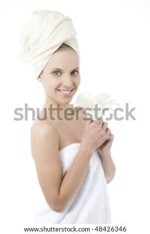 Beauty wrapped in towel holding a flower - stock photo