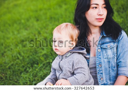Beauty young asian woman mom with freckles and her son relaxing outdoors. Mother brunette with dark hair and her son is blond. Unusual appearance and heredity concept. Copy space - stock photo