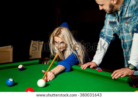 Beauty young blonde woman plays billiard for the first time with a teacher. Billiard sport concept. American pool billiard. Pool billiard game. - stock photo