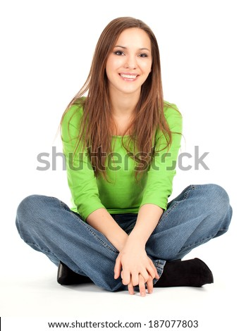beauty young girl sitting on the floor with crossed legs, smiling, full lenght, white background - stock photo