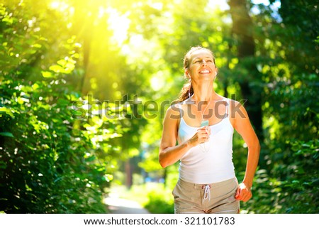 Beauty young smiling woman running outdoor over sunrise. Brunette model girl jogging in the park and enjoying nature. Female training and listening to music by headphones. Workout. Healthy lifestyle - stock photo