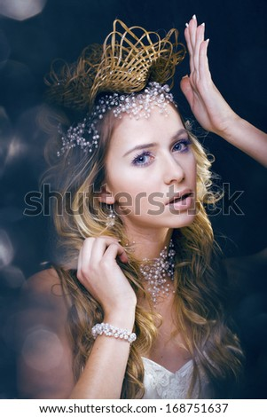 beauty young snow queen in fairy flashes with crown on her head - stock photo