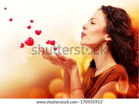 Beauty Young Woman Blowing Hearts from her Hands. St. Valentines Day Concept. Beautiful Girl in Love. Valentine art design. Valentines Gift - stock photo