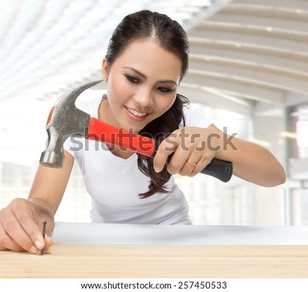 beauty young woman construction worker put nail on the wood using hammer - stock photo