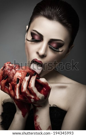 Beauty young woman licks blood from human heart against grey background - stock photo
