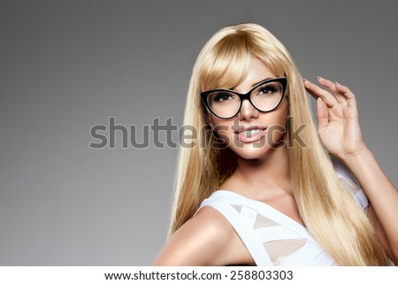 Beauty young woman luxury long blond hair in glasses Haircut, fringe Girls fresh healthy skin, makeup lips, eyelashes, manicured nails shiny. Fashion model in spa care salon Sexy trendy hairstyle look - stock photo