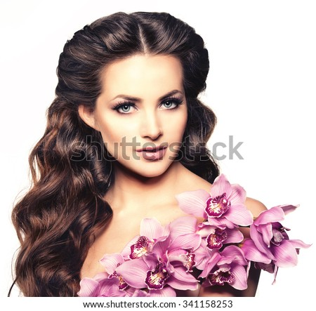 Beauty young woman, luxury long curly hair with orchid flower. Haircut. Beautiful woman fresh healthy skin, makeup, lips, eyelashes. Fashion model in spa care salon. Sexy trendy hairstyle look. - stock photo