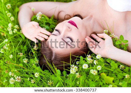 Beauty young woman lying on the grass and dreaming - stock photo