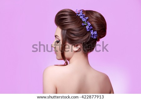 Beauty young woman with flowers in hair. Perfect face skin and makeup. Healthy dark hair decorated with flowers. Beautiful Woman Portrait on pink background. Hair care concept - stock photo