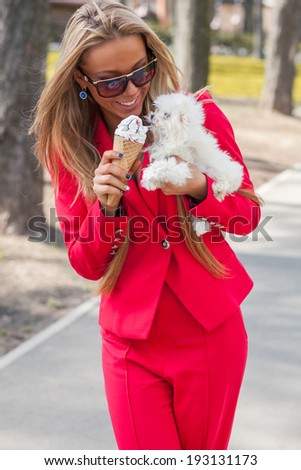 Beauty young woman with icecream and little puppy - stock photo