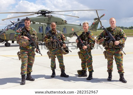 BEAUVECHAIN, BELGIUM - MAY 20, 2015: Belgian army soldiers in front of the new NH90 helicopter during the THPU exercise. THPU is an annual helicopter evaluation excercise. - stock photo