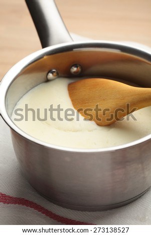 Bechamel in a sauce pan with wooden spoon - stock photo