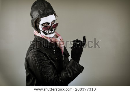 Beckoning aviator with face painted as human skull - stock photo