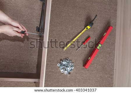 Bed frame assembly, furniture builder hands fix the screw using a screwdriver, nearby is the tool level, tape measure and fasteners. - stock photo