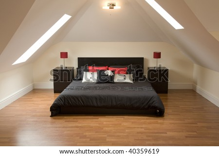 bed in a loft bedroom that looks really comfy - stock photo